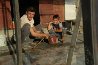 A father teaches his son tile making.